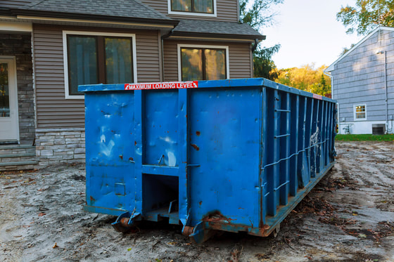 blue 30 yard dumpster in front of new home