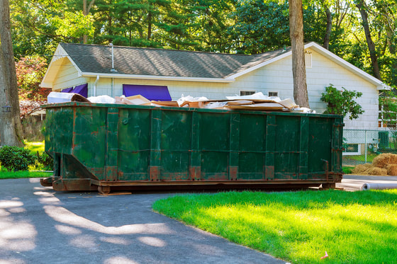 green 20 yard dumpster on a driveway